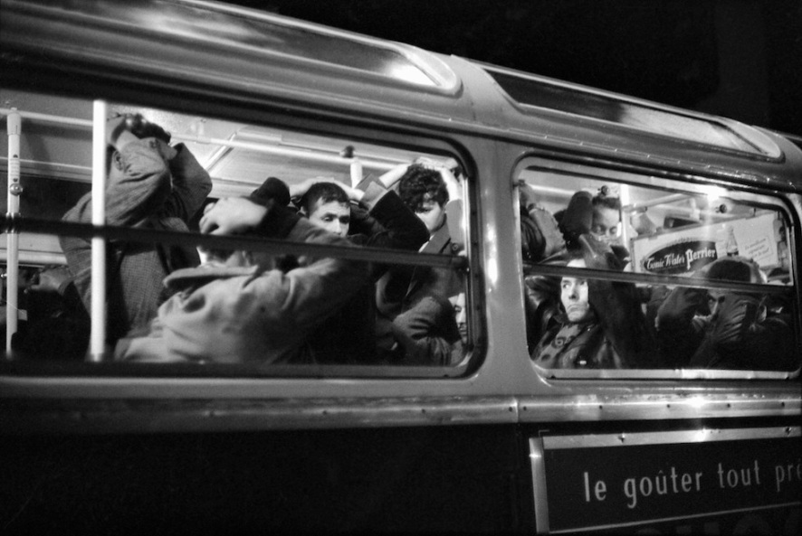 "Paris, FRANCE: (FILES) This file picture taken 17 October 1961 in Paris shows Algerian emigrants holding their hands on their heads in a bus after they were arrested by French police during a brutal police crackdown where dozens of Algerian protesters -- some witnesses spoke of 200 -- were killed by police. More than 40 years after the massacre and for the first time, a French fiction movie about the 17 October 1961 events was broadcasted on French television in June 2005. ""Nuit Noire"" (dark night), which breaks a taboo in the French recent history, will be also released 19 October in theaters, in DVD, and will be re-broadcasted six times on Canal +. AFP PHOTO/FILES (Photo credit should read ARCHIVES/AFP/Getty Images)"